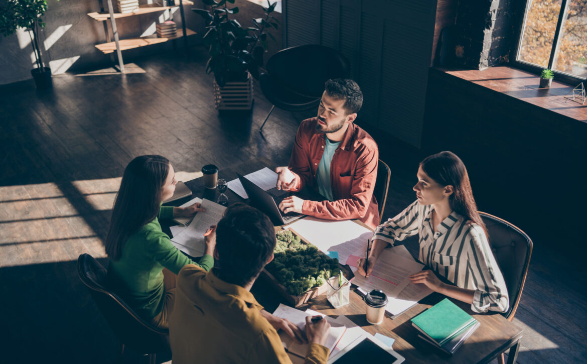 Four busy experienced businesspeople wearing casual formal-wear discussing delegation company growth income at modern industrial loft wooden interior workplace workstation